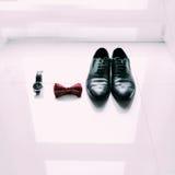 Skor, fluga och klocka för brudgum` s på ljus fönsterbakgrund Royaltyfria Foton