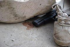 Skor/gymnastikskor och vapen av den dödade mannen arkivbilder