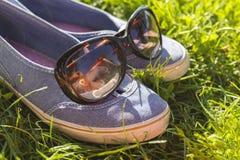 Skor gymnastikskor på gräset med solglasögon, sommaravkoppling och avbrottsbegrepp Fotografering för Bildbyråer