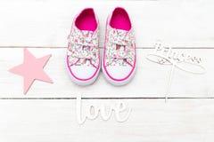 Skor och inskrifter för rosa färger för barn` s på en vit träbackgro royaltyfria bilder