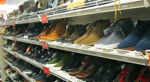 Skor och kängor som är till salu i ett lager eller, shoppar Arkivfoto