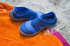 Skor på en strandhandduk Fotografering för Bildbyråer
