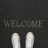 Skor på välkommen matta Royaltyfri Foto