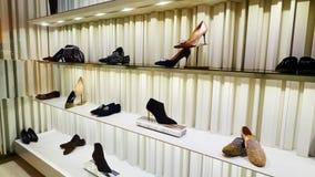 Skor shoppar in lagerfönstret Arkivfoton