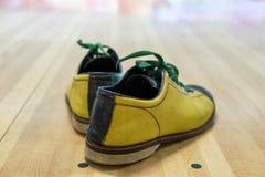 Skor som bowlar gul gräsplan på trä Arkivbild