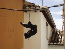 Skor som hänger från en kabel Fotografering för Bildbyråer