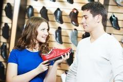 Skor som shoppar i skodonlager arkivbilder