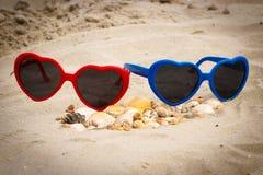 Skorupy i okulary przeciwsłoneczni w kształcie serce na piasku przy plażą, sezonowy pojęcie Zdjęcia Royalty Free