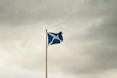 Skotsk flagga mot mulna himlar Fotografering för Bildbyråer