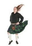 Skotsk man i traditionell nationell dräkt med att blåsa kilten arkivbild