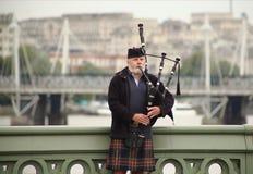 Skotsk säckpipeblåsare på den Westminster bron Royaltyfri Bild