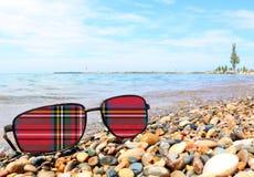 Skotsk tartan på solglasögonlinser royaltyfria foton
