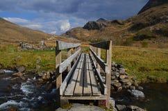 Skotskt landskap, dal och träbro över floden Royaltyfri Foto