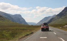 Skotskt Skotska högländernalandskap i sommar - gammal bil på vägen i dalen Arkivbild