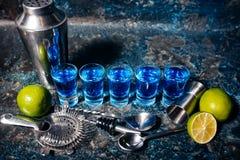 Skott av blåa curacao alkoholdrycker, blå coctailar för skott och limefrukt royaltyfri foto