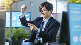 Skott av den lyckliga östliga asiatiska affärsmannen Winning i mobil lek royaltyfria foton