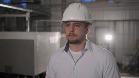 Skott av den yrkesmässiga fabriksarbetaren som bär för hållminnestavla för hård hatt som datoren går Thorugh modernt industriellt stock video