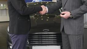 Skott av en bilåterförsäljare och hans klient som skakar händer Yrkesmässig representant som ger biltangenter till hans dela för  arkivfilmer