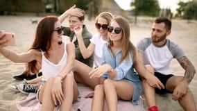 Skott av en grupp av unga vänner som tar en selfie på stranden Män och kvinnor som tar foto som sitter på en sand på varmt stock video
