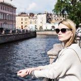 Skott av en härlig kvinna som står en liten bro över kanalen medan på sight i en utländsk stad arkivfoton