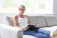 Skott av en mogen kvinna som läser hennes favorit- roman medan hemma i vardagsrum arkivfoton