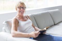 Skott av en mogen kvinna som läser hennes favorit- roman medan hemma i vardagsrum royaltyfria foton