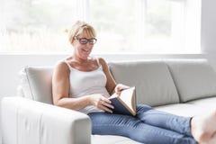 Skott av en mogen kvinna som läser hennes favorit- roman medan hemma i vardagsrum arkivbild