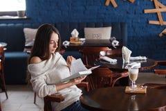 Skott av en ung stilfull kvinna som använder en digital minnestavla i ett kafékaffe och en stor bok Goda för liv` s Royaltyfri Bild