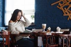 Skott av en ung stilfull kvinna som använder en digital minnestavla i ett kafékaffe och en stor bok Goda för liv` s Arkivbilder