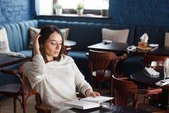 Skott av en ung stilfull kvinna som använder en digital minnestavla i ett kafékaffe och en stor bok Goda för liv` s Royaltyfria Bilder