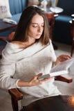 Skott av en ung stilfull kvinna som använder en digital minnestavla i ett kafékaffe och en stor bok Goda för liv` s Arkivbild