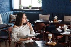 Skott av en ung stilfull kvinna som använder en digital minnestavla i ett kafékaffe och en stor bok Goda för liv` s Royaltyfri Fotografi