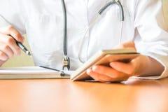Skott av kvinnliga händer för doktors` s genom att använda den smarta telefonen Professionelln är bläddra och söka information royaltyfria foton