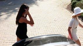 Skott av kvinnor som går in i en shoppa från en parkerad bil lager videofilmer