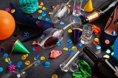 Skott för bästa sikt av efter en partiberöm med tomglas, vinexponeringsglas, flickaskor och partigarnering royaltyfri fotografi