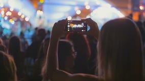 Skott för bakre sikt av fans som gör video av konsert på natten arkivfilmer