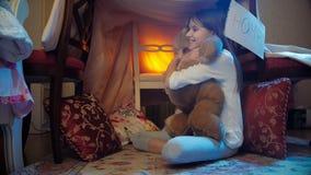 skott för docka 4k av den gulliga flickan i pyjamas som spelar med nallebjörnen i selfmade hus arkivfilmer