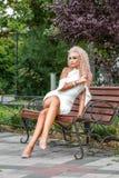 Skott för högt mode av den unga blonda kvinnan i den vita korta klänningen royaltyfri bild