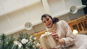 Skott för låg vinkel av den upphetsade för studentöppning för ung dam som asken för låda ser hennes gåva som uttrycker spänning o lager videofilmer