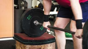 Skott för låg vinkel på mans ben göra squats med den olympiska stången stock video