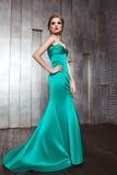 Skott för modeskönhetfoto av den härliga modellen i grön klänning med makeup och frisyren Royaltyfri Bild
