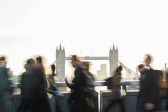 Skott för rörelsesuddighet av pendlare som går för att arbeta över den London bron UK med tornbron i bakgrund fotografering för bildbyråer