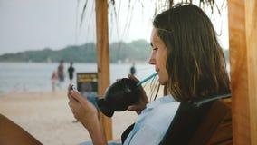 Skott för sidosikt av den unga avkopplade freelancerkvinnan med hållande ögonen på video för exotisk drink på smartphonen i varda arkivfilmer