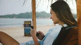 Skott för sidosikt av den unga avkopplade freelancerkvinnan som använder smartphonen som shoppar appen i vardagsrumstrandstol med lager videofilmer