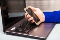 Skott för sidosikt av mans händer genom att använda den smarta telefonen i inre bakre sikt av affären arkivbild