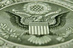 Skott för sned vinkel av baksidan av USA en dollarräkning som presenterar den amerikanska örnen arkivfoto