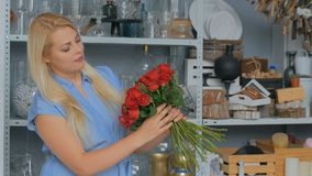 2 skott Hållande bukett för yrkesmässig blomsterhandlare av röda rosor på studion arkivfilmer
