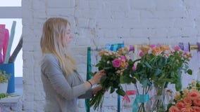 3 skott Yrkesmässig blomsterhandlare som gör den härliga buketten på blommalagret lager videofilmer