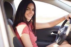 Skottet åt sidan av den angenäma seende brunettkvinnan sitter i hennes egen bil, uppehällehänder på hjulet, tycker om hög hastigh royaltyfria foton