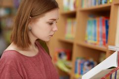 Skottet åt sidan av den klyftiga allvarliga kvinnliga studenten ser uppmärksamt på boken, står i universitetarkiv, väljer nödvänd fotografering för bildbyråer